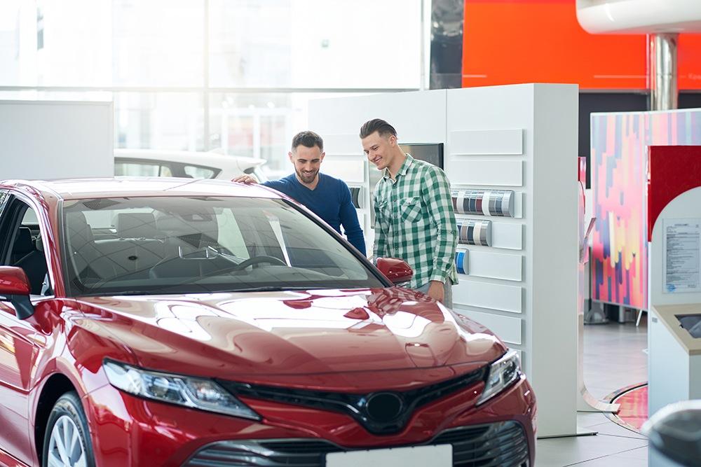 Car seller showing customer car in dealership.